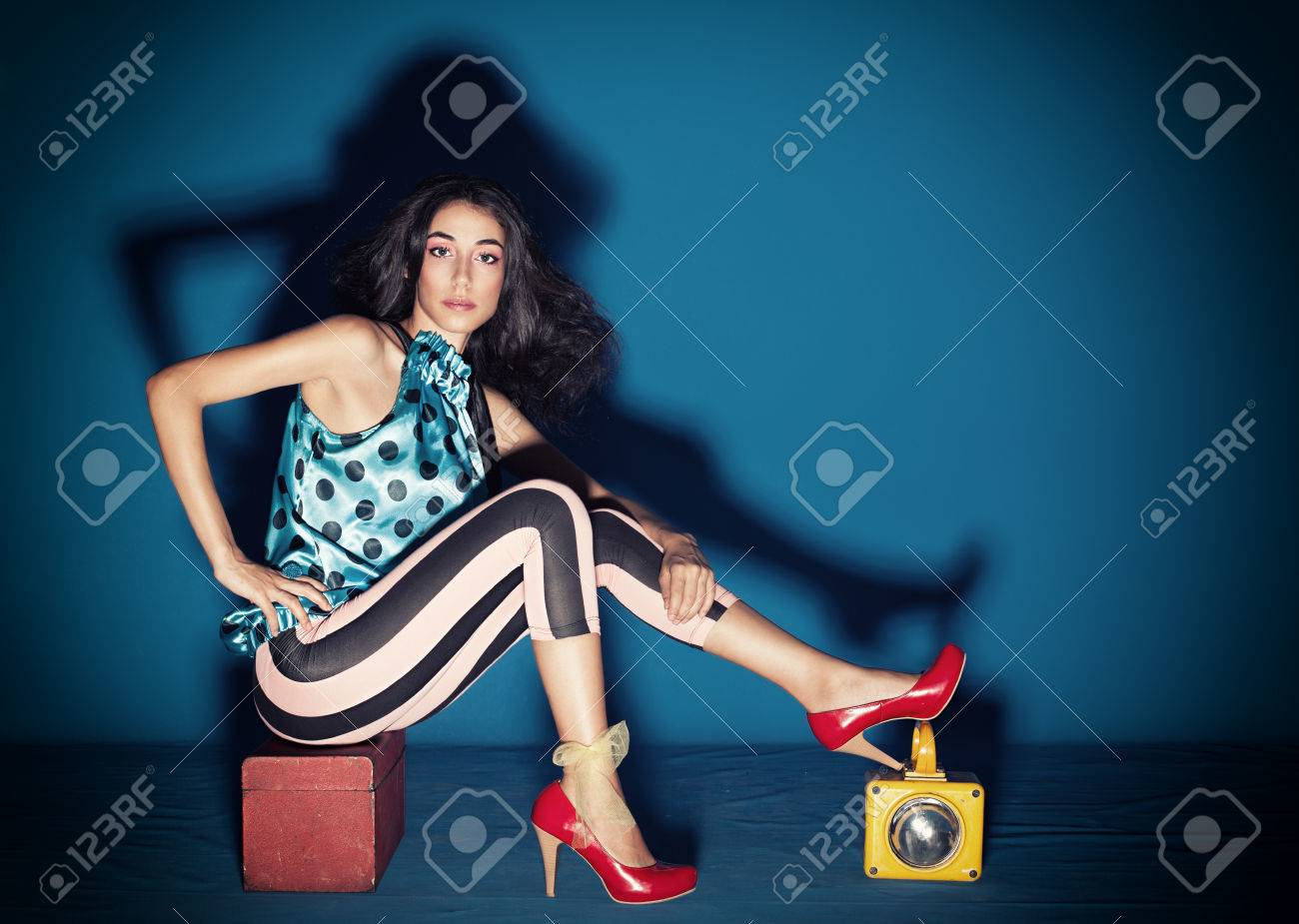 beautiful young model with colorful clothes posing on blue background Stock Photo - 24962455