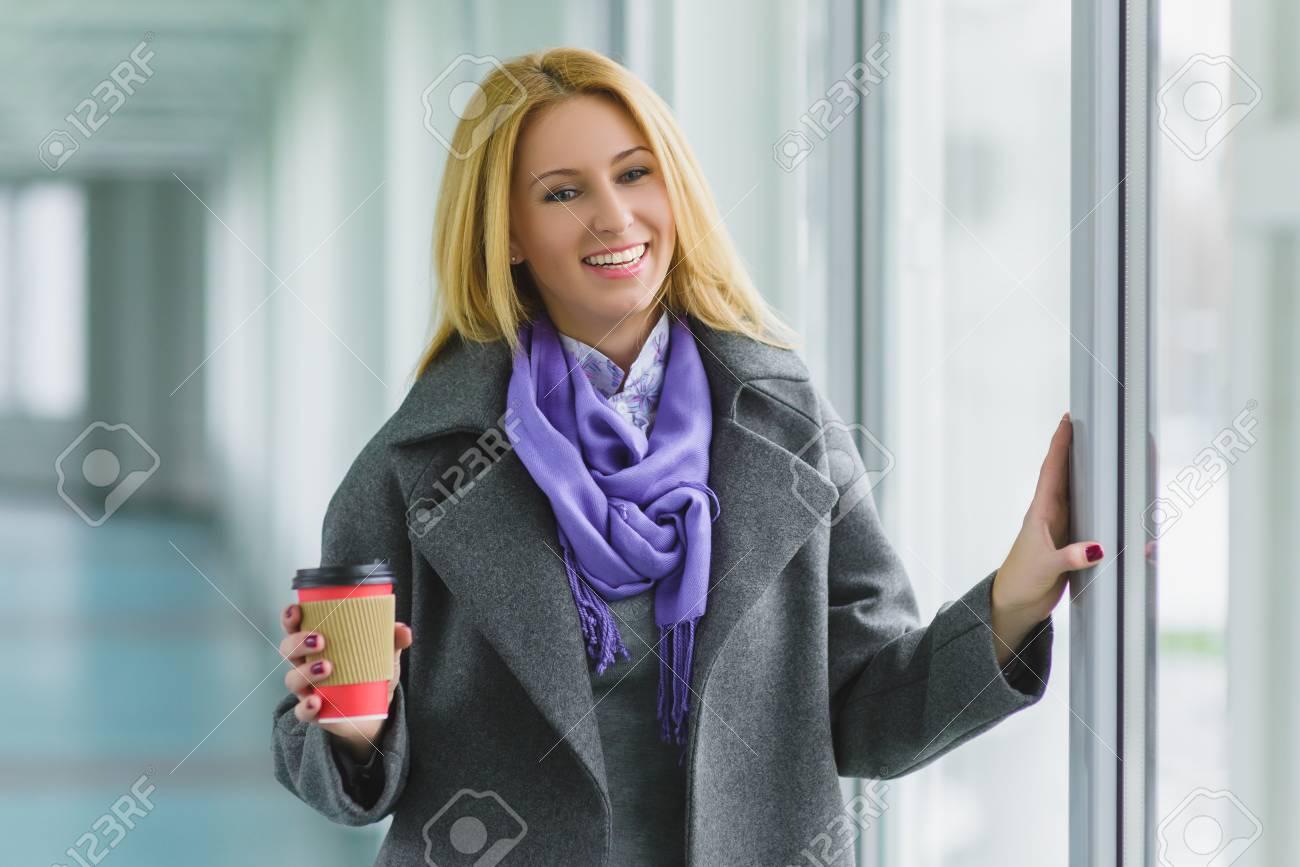Femme habillée porte manteau dans le hall