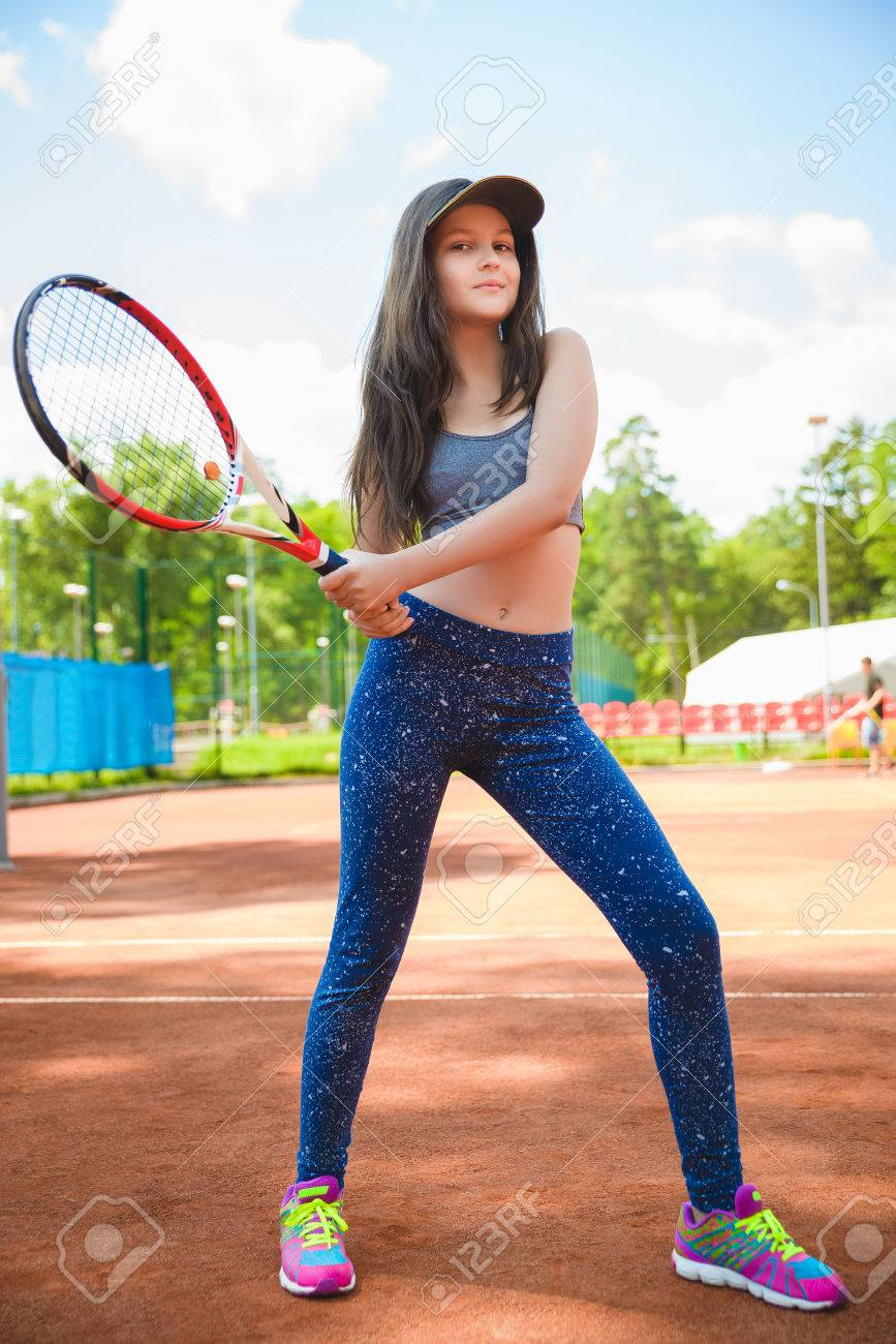 Cute Girl Playing Tennis And Posing In Court Outdoor Stock Photo