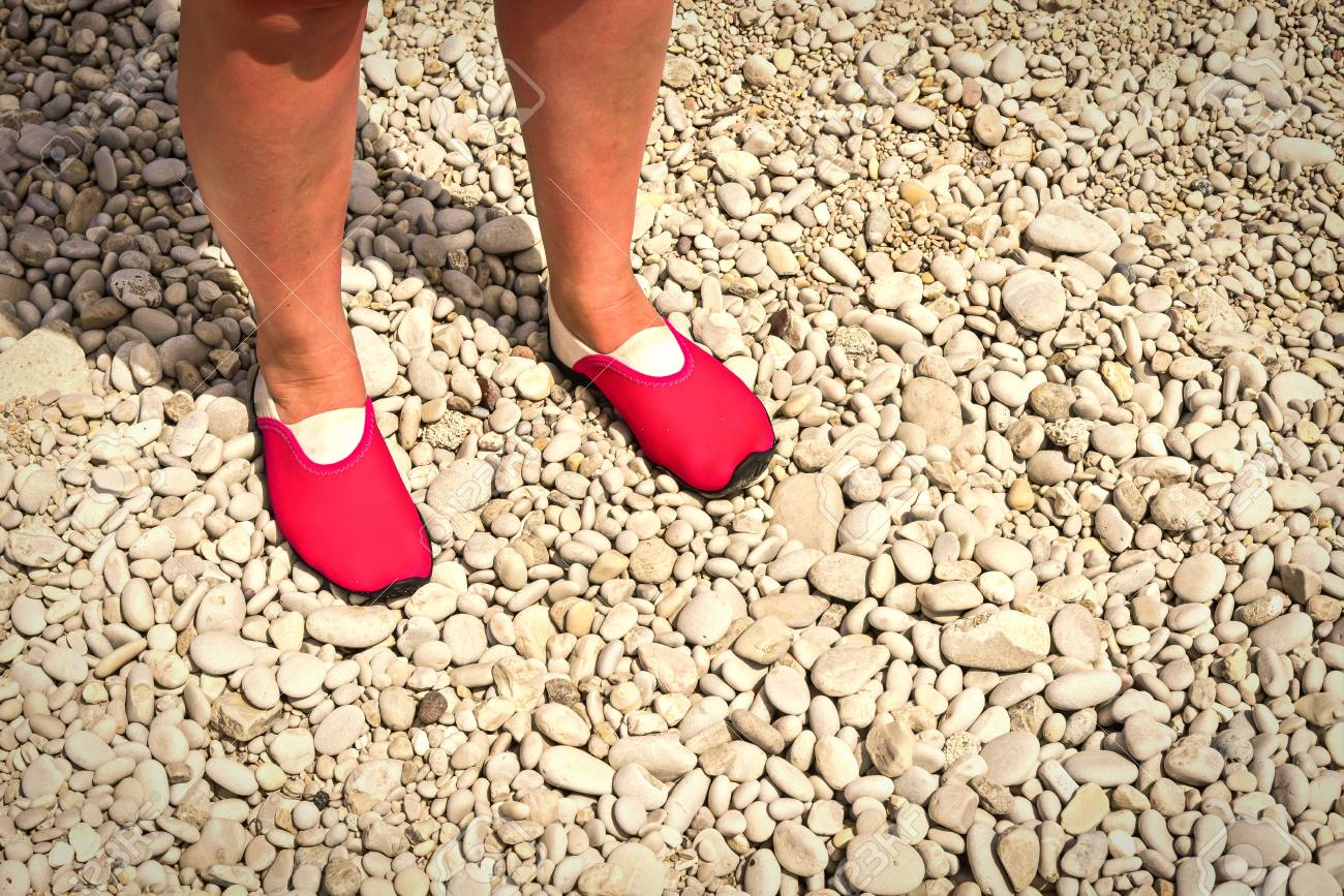 598d33268a2d Stock Photo - Water shoes   swimming shoe in pink color on pebbles on beach.