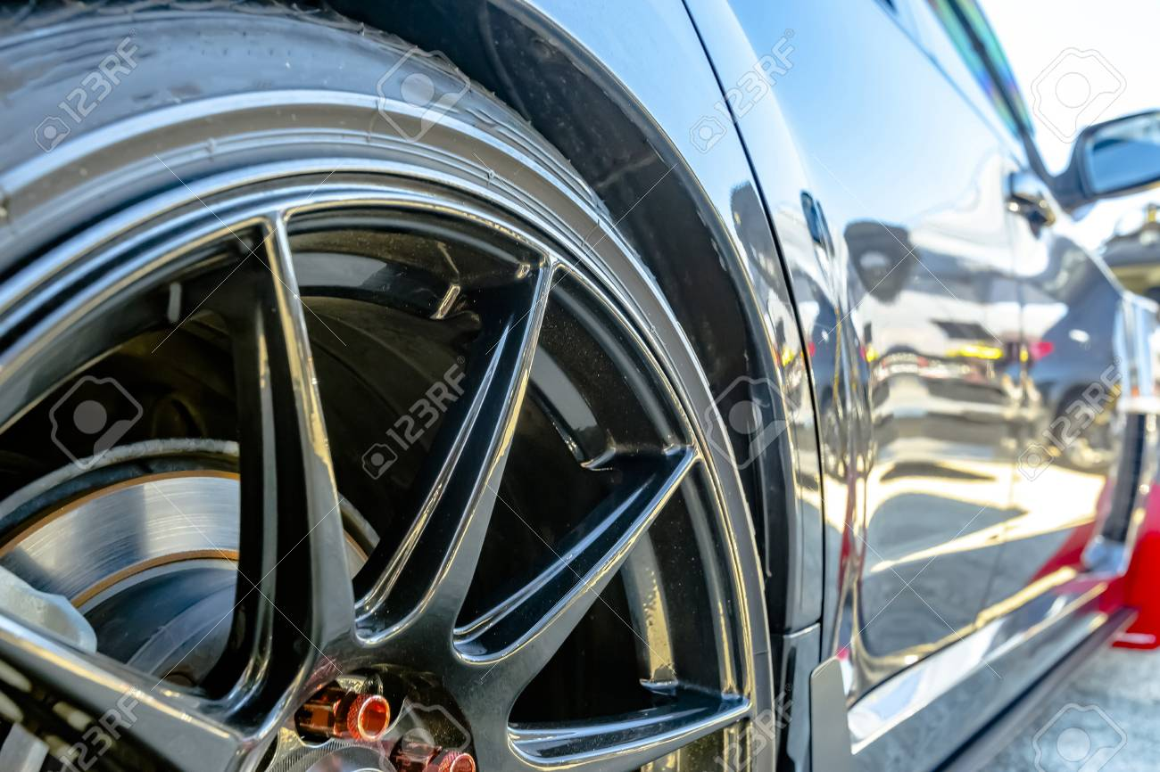 Tires with black rims on a black car with red bolts  Various