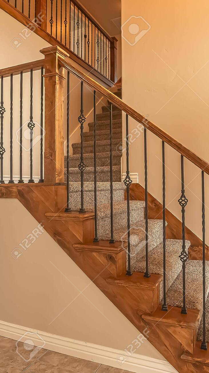 Vertical frame Carpeted stairs with wood handrail and metal railing..