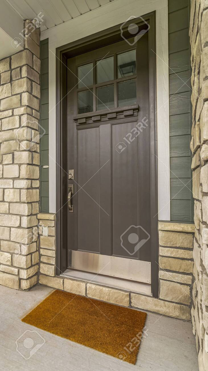 Vertical Home Entrance With A Glass Paned Brown Wooden Door And
