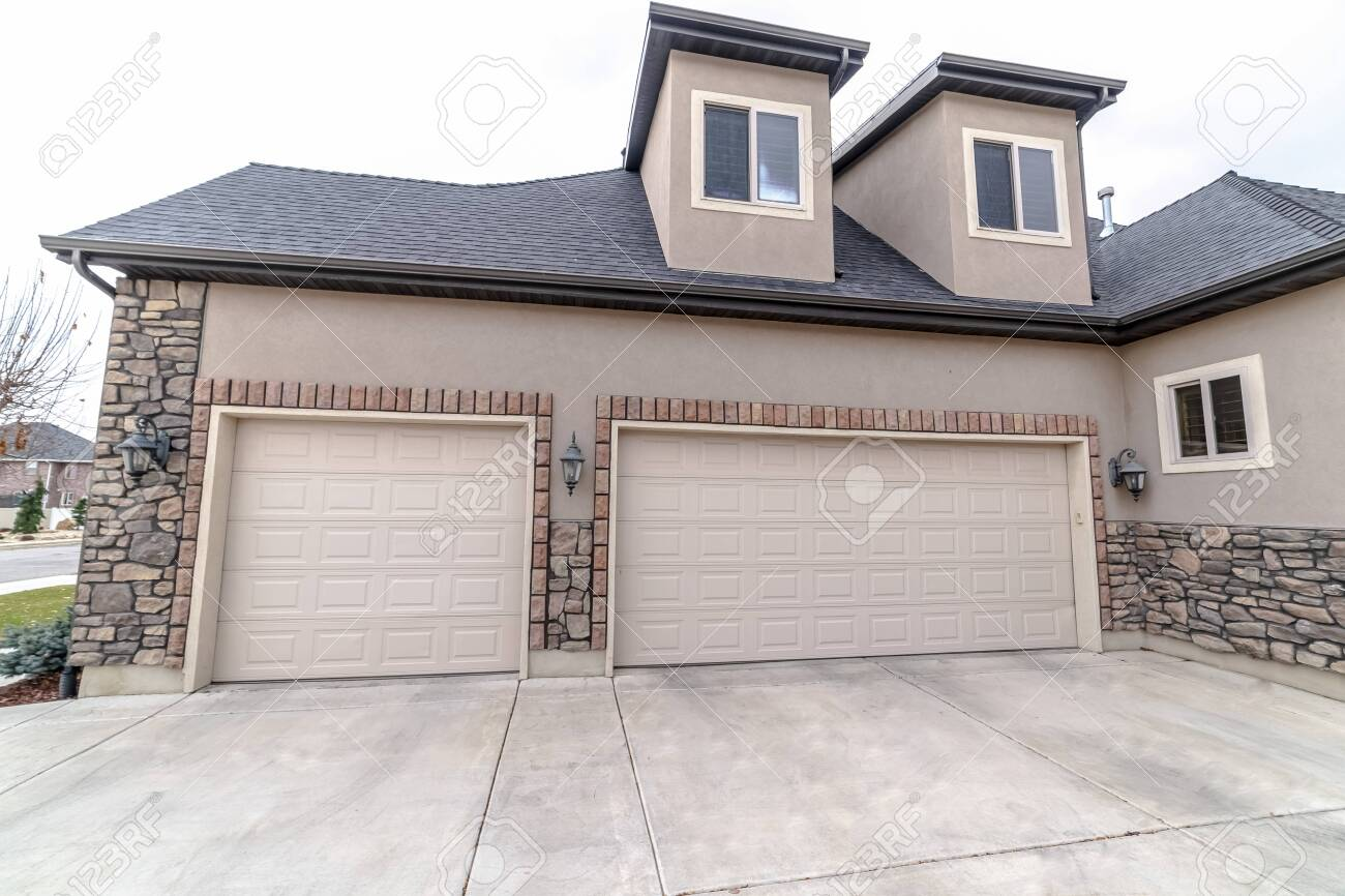 Urban house with a single and double garages with concrete driveway in close up view - 137673835