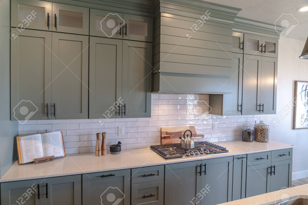 - Wooden Cabinets And White Counter Top Inside A Kitchen With Tile