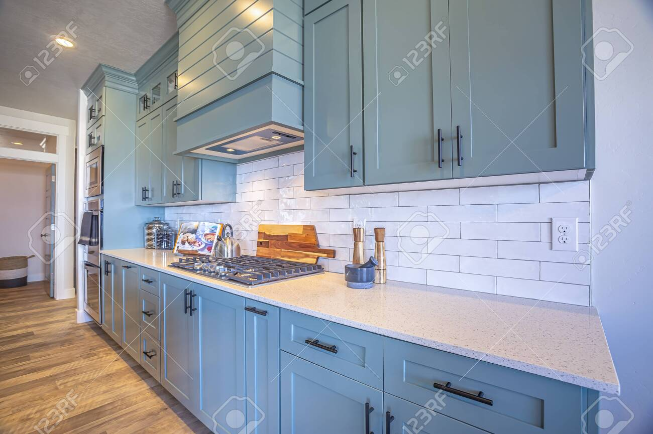 - Kitchen With White Counter Top And Bluish Gray Cabinets Against
