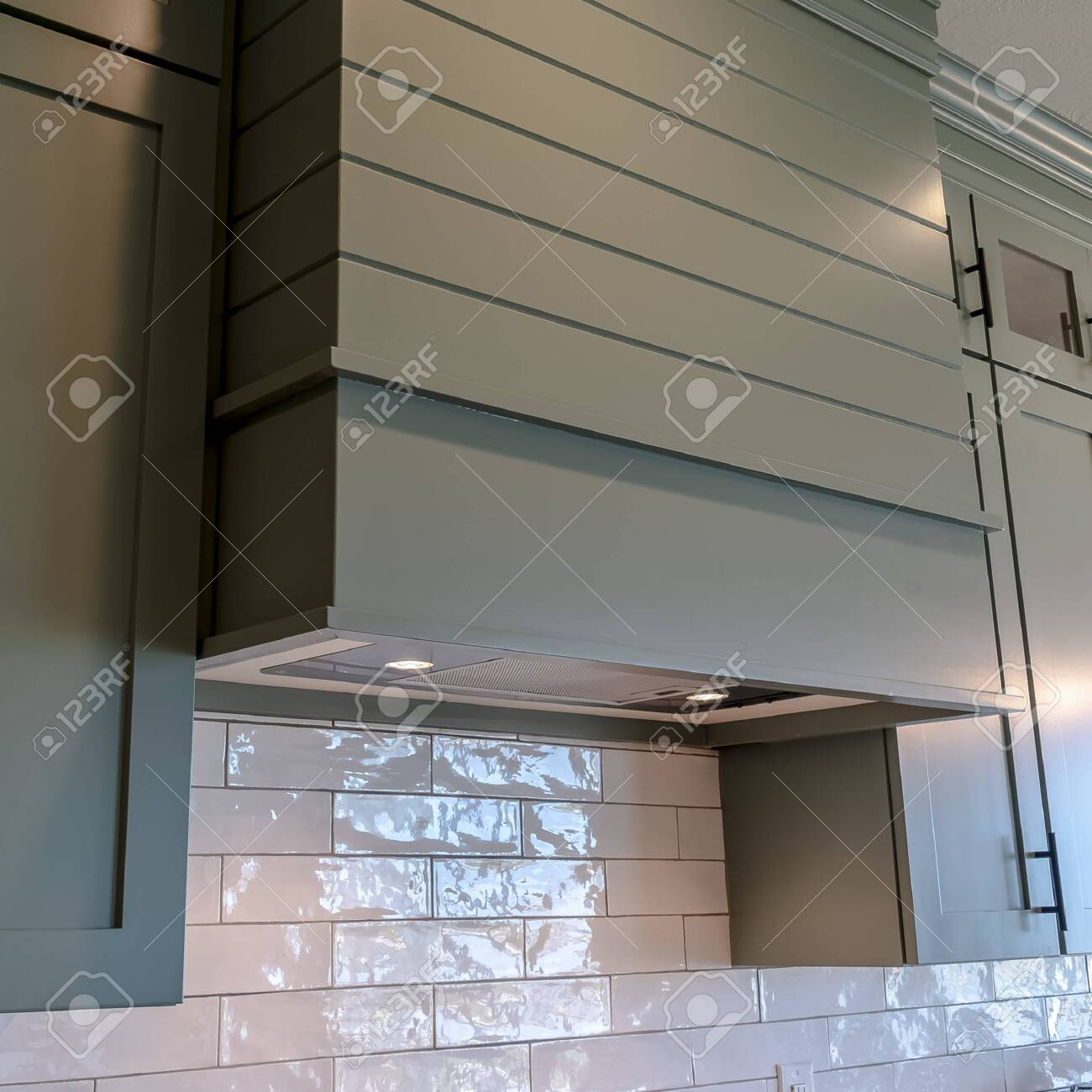 - Square Frame Kitchen Interior With Hanging Cabinets Against Tile