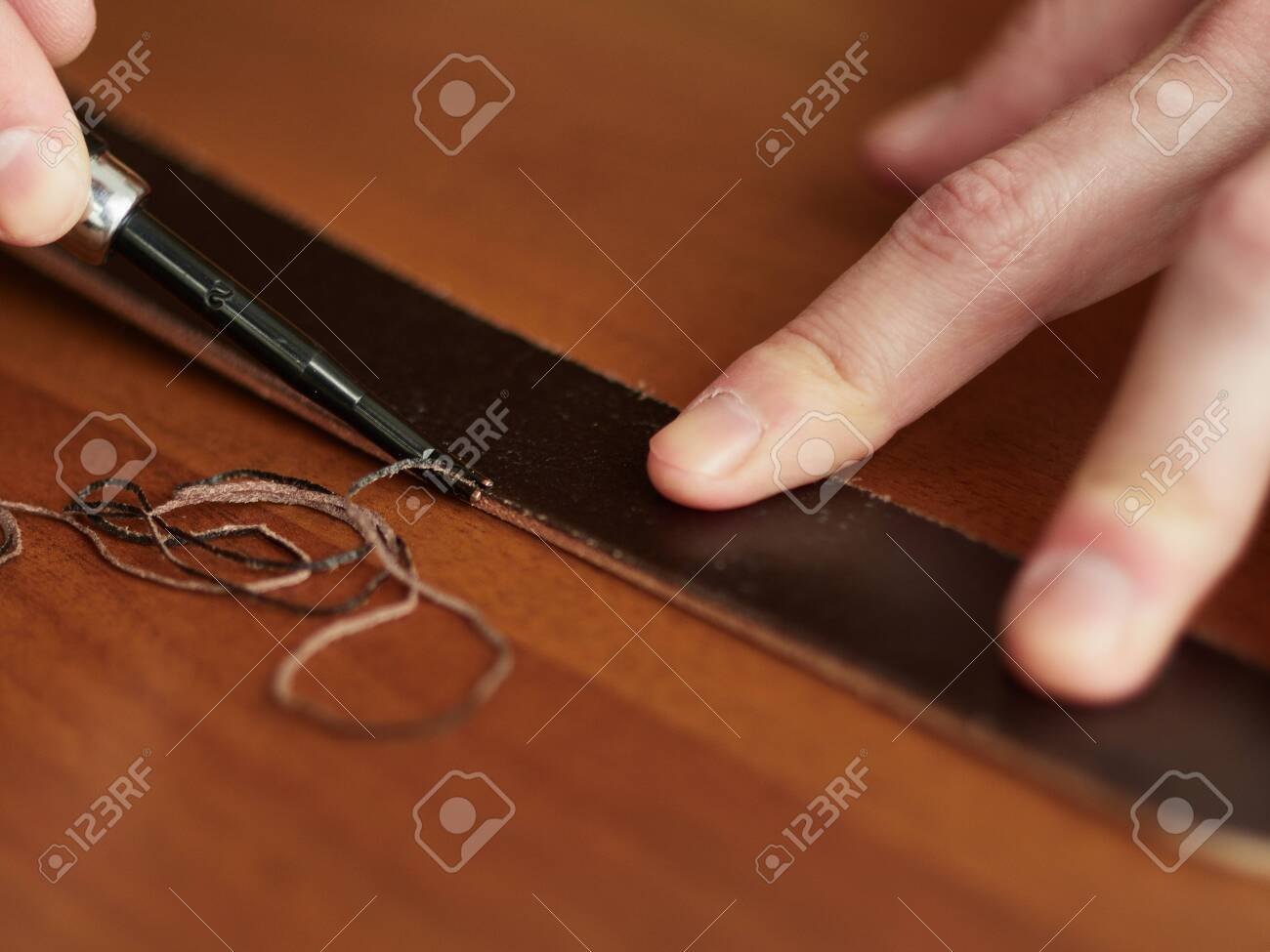 Chamfering with a leather belt by a tanner. - 126245931