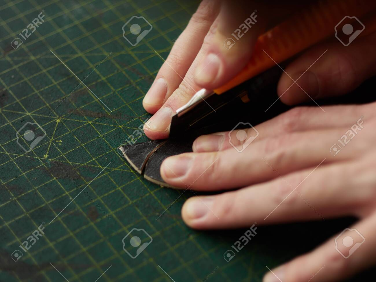 Shaping the tip of the leather strap with a knife. - 131722426