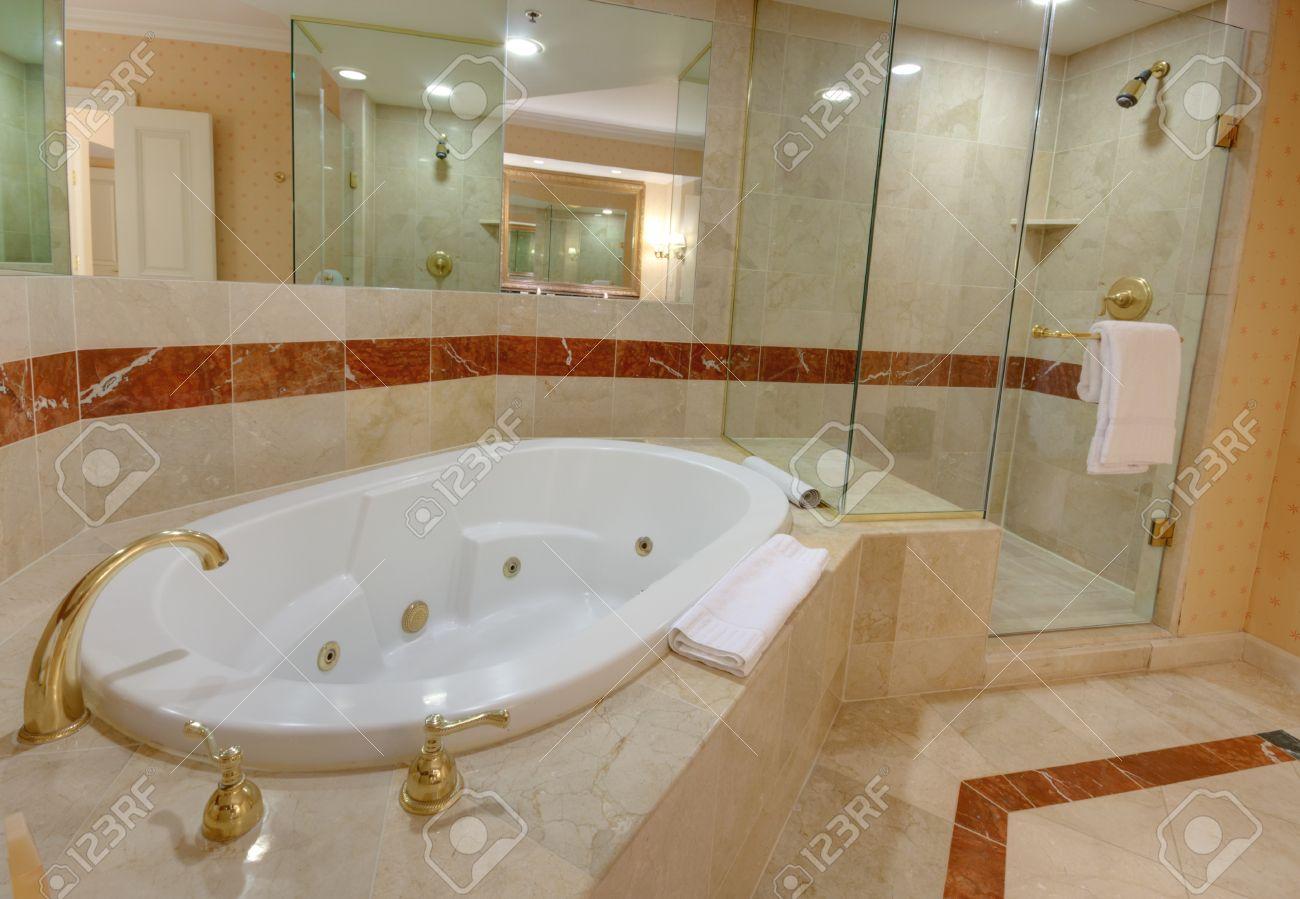 baignoire jacuzzi blanc et robinets en laiton décorée de carreaux de