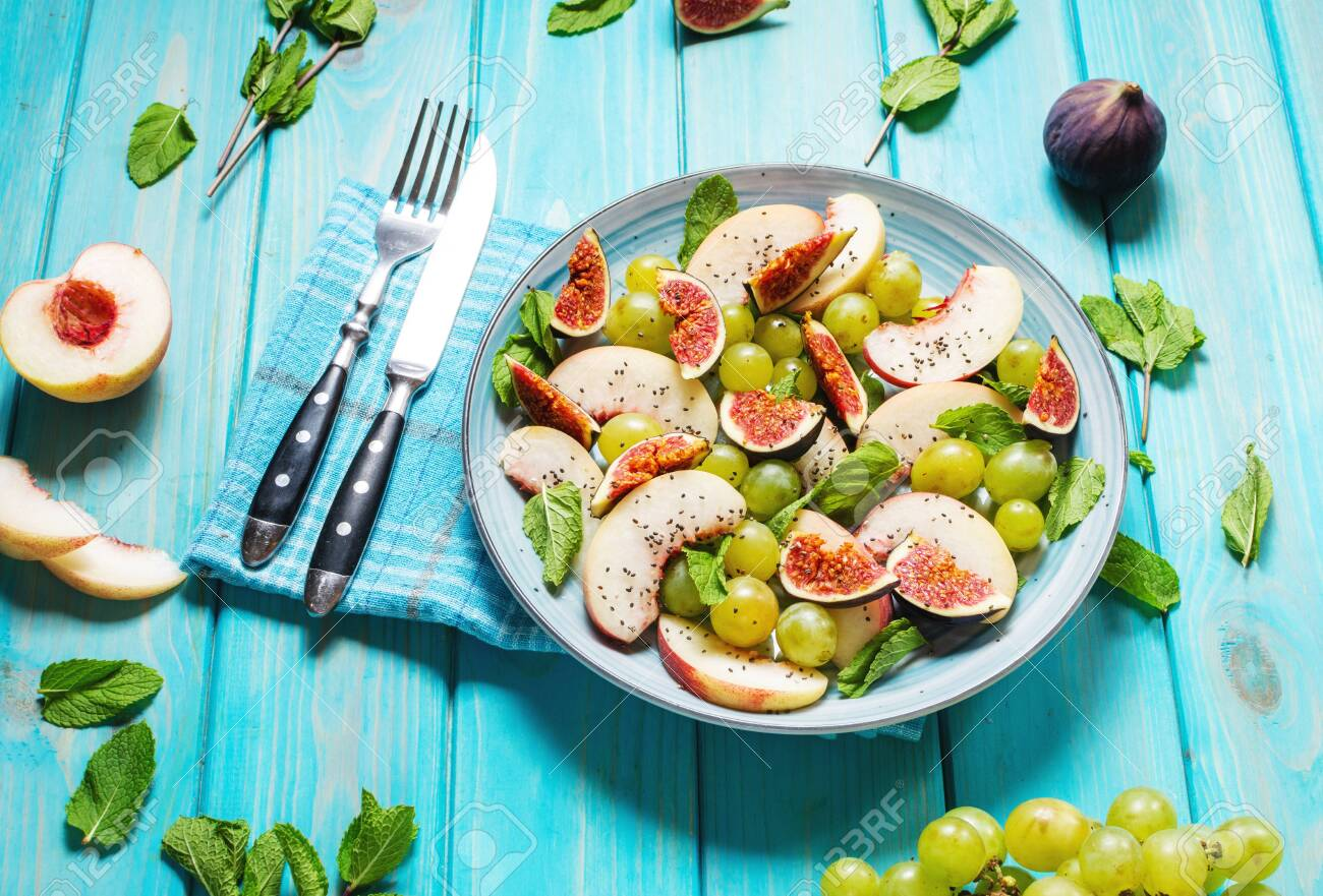 Fresh fruit and berry salad with grapes, fig and peach on blue wooden background. Healthy food. - 131142447