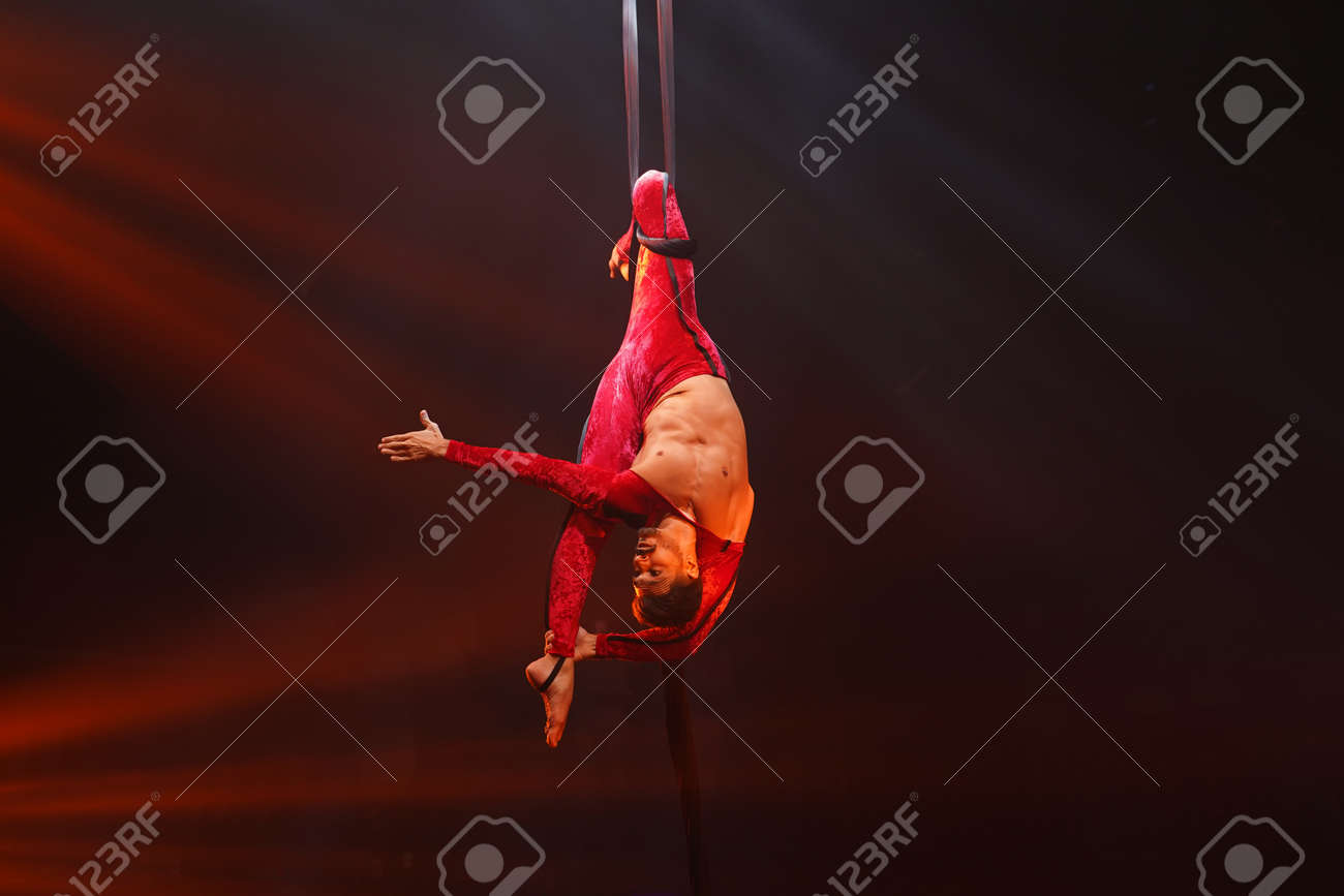 Brazilian strong man do stretching acrobat element upside down on aerial silks in red lights. - 169238178