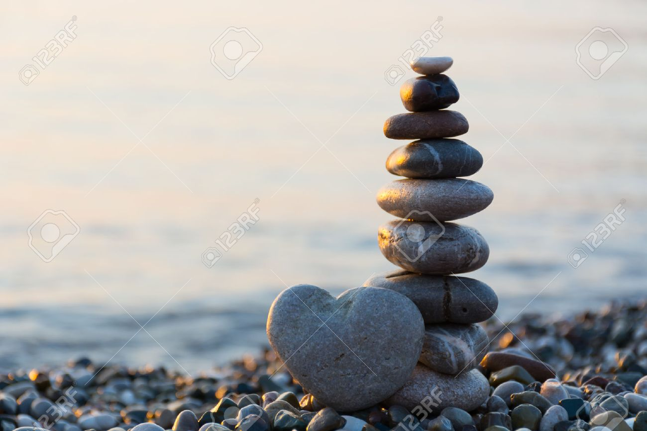 Grey stone in shape of heart in front of balanced stones on still water background - 52034738