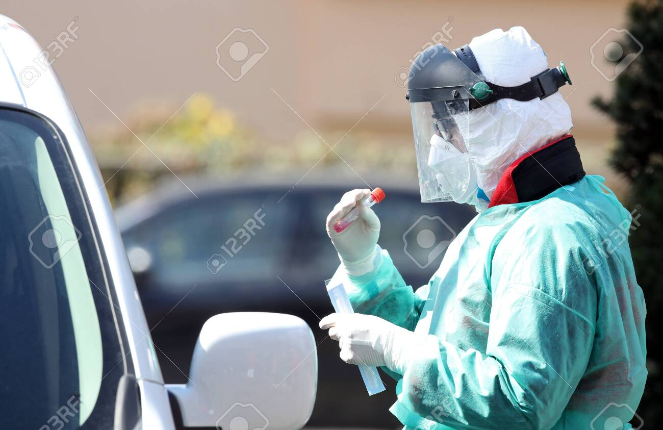 Medical staff member with mask and protective equipment performs Coronavirus nasal swabs test tubes at drive-through testing point in an effort to curb the spread of COVID-19 (novel coronavirus) - 144570144