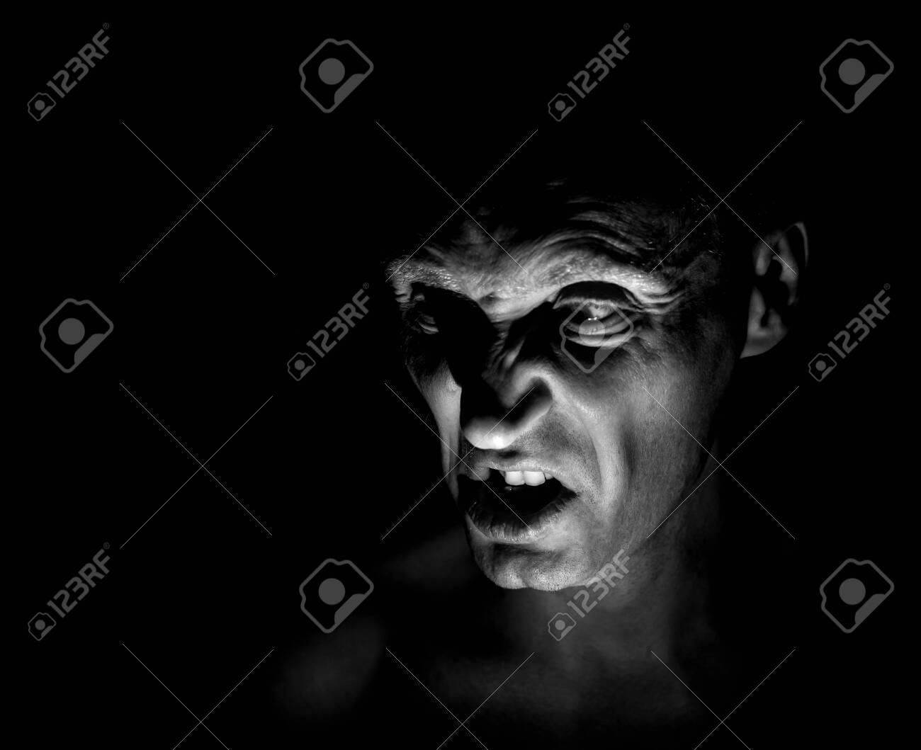 Stylish portrait of adult caucasian man with very angry face and who seems like maniac or devil. He screams at someone. Black and white shot, low-key lighting. Angry man, fear concept. - 122083355