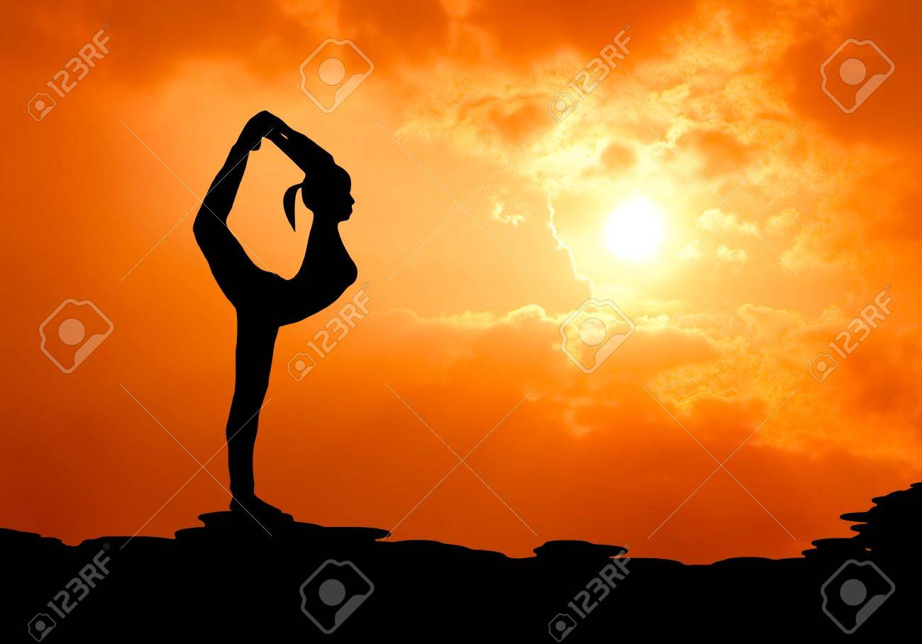 beautiful woman practise yoga at sunset silhouetted Stock Photo - 13224489