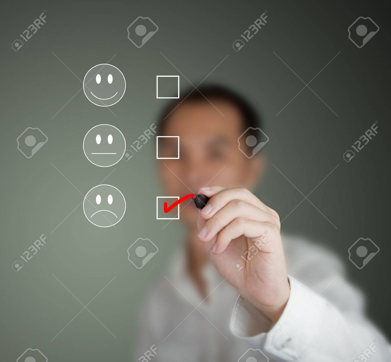 business man marking at unhappy mood on customer satisfaction survey form Stock Photo - 13225084