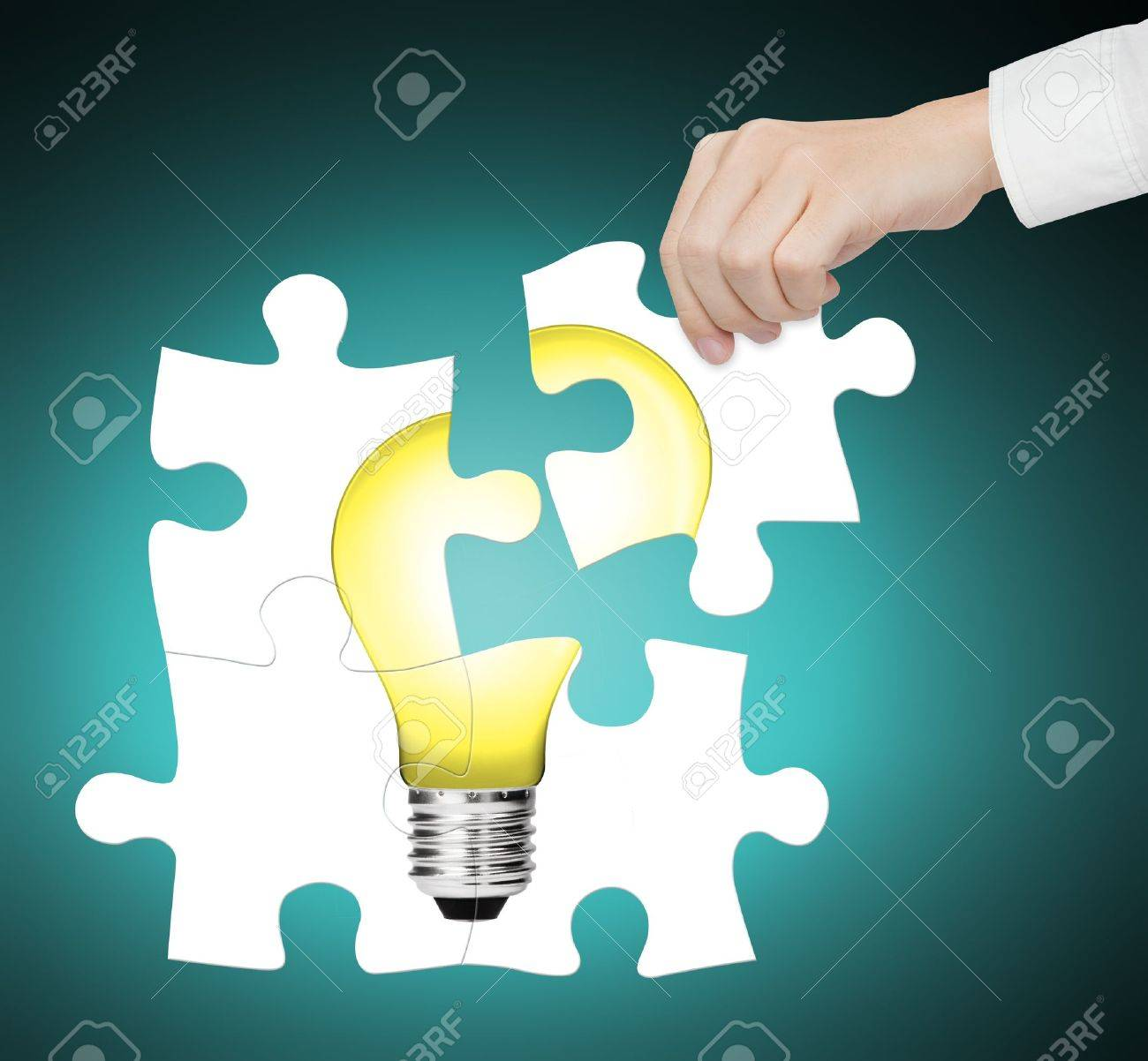 hand completing jigsaw puzzle of  light bulb, sign of idea, innovation, creative, smart, vision, solution, energy, electric etc. Stock Photo - 13549955