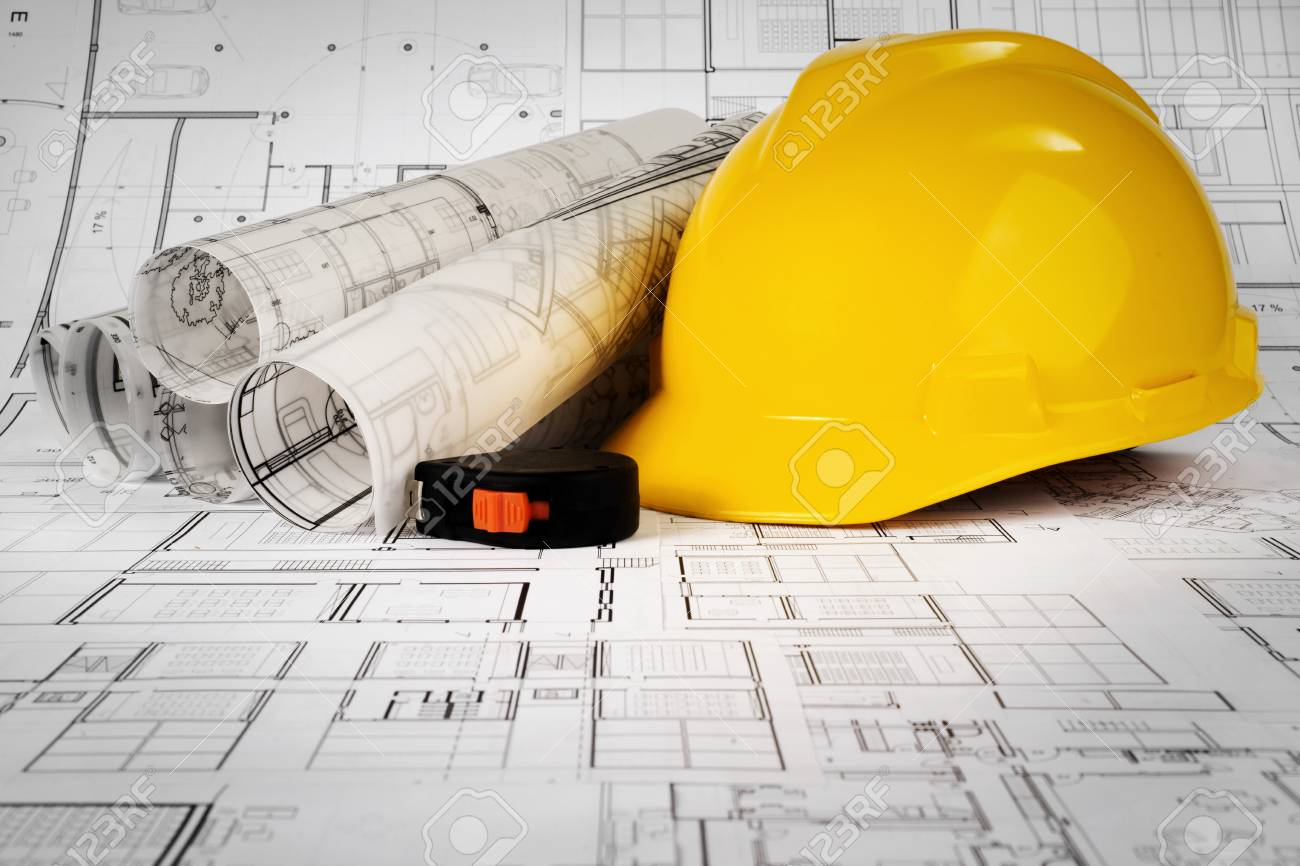 Yellow helmet, tape measure and project drawings - 99972369