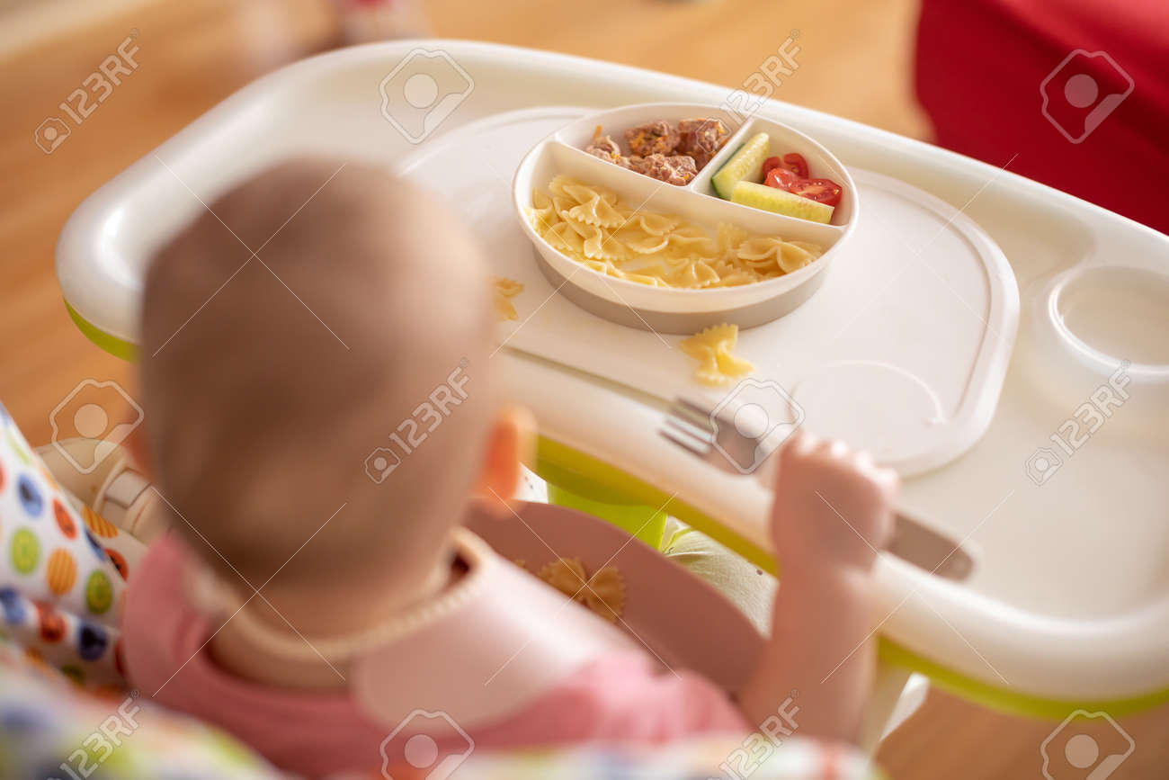 One year old girl having balanced meal in baby eating chair, healthy balanced nutrition for child, pasta, cutlet and vegetables - 166397459