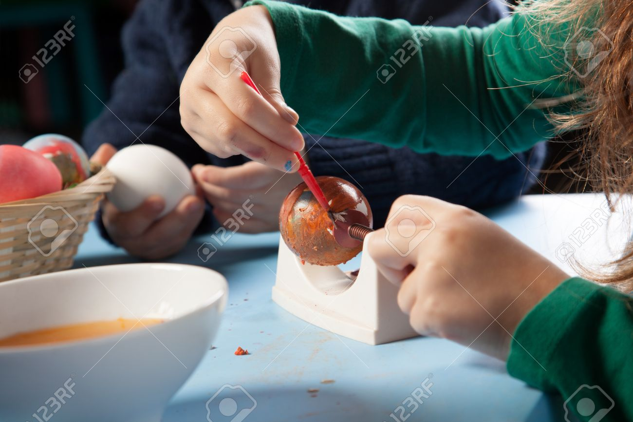 Cropped view image of the hands of a young girl carefully painting traditional Easter eggs in colourful patterns Stock Photo - 18097428