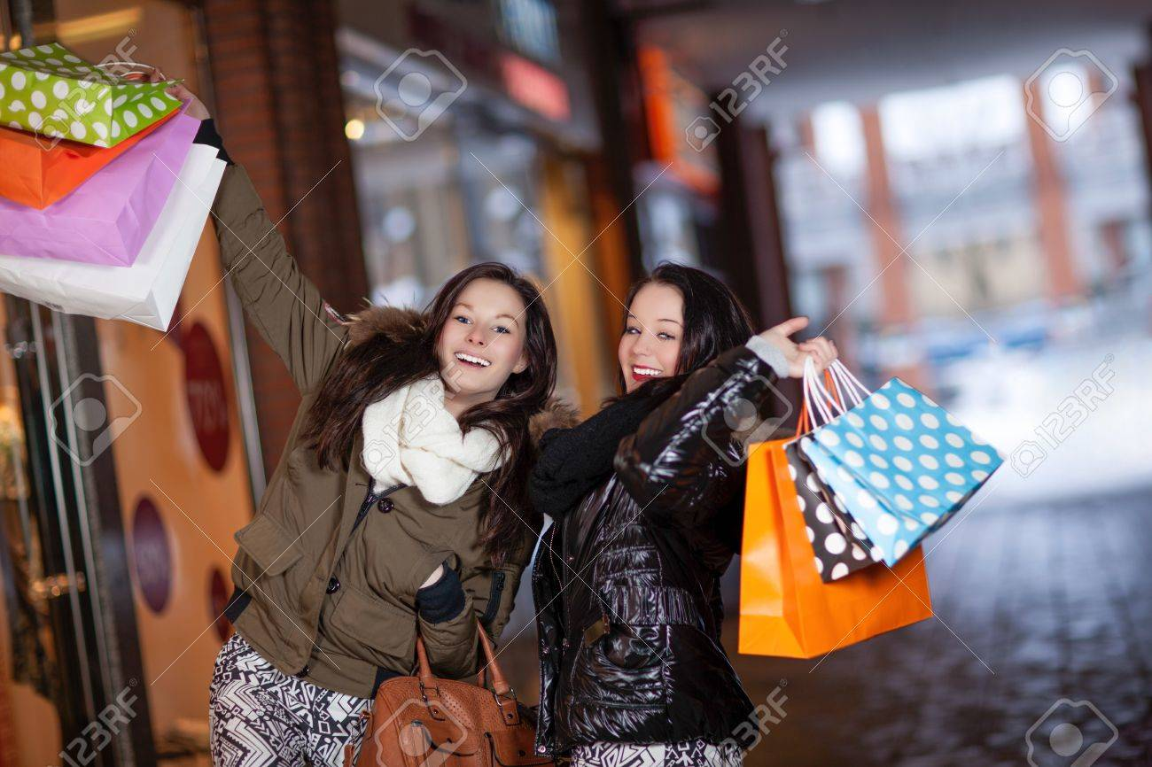 Playful beautiful young female shoppers with lots of purchases standing together in a mall laughing and holding their shopping bags up in the air Stock Photo - 18381602