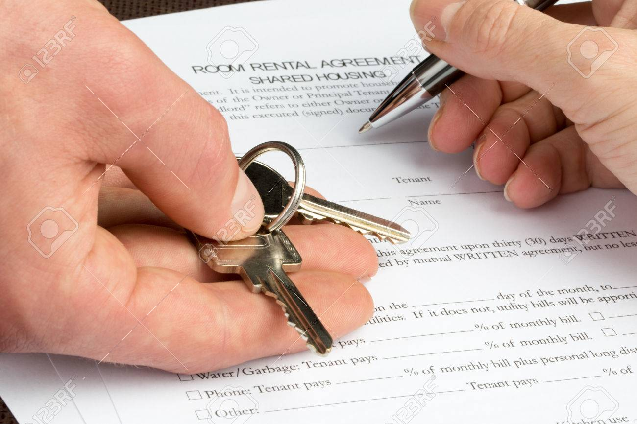 A woman is filling out a room rental agreement document with