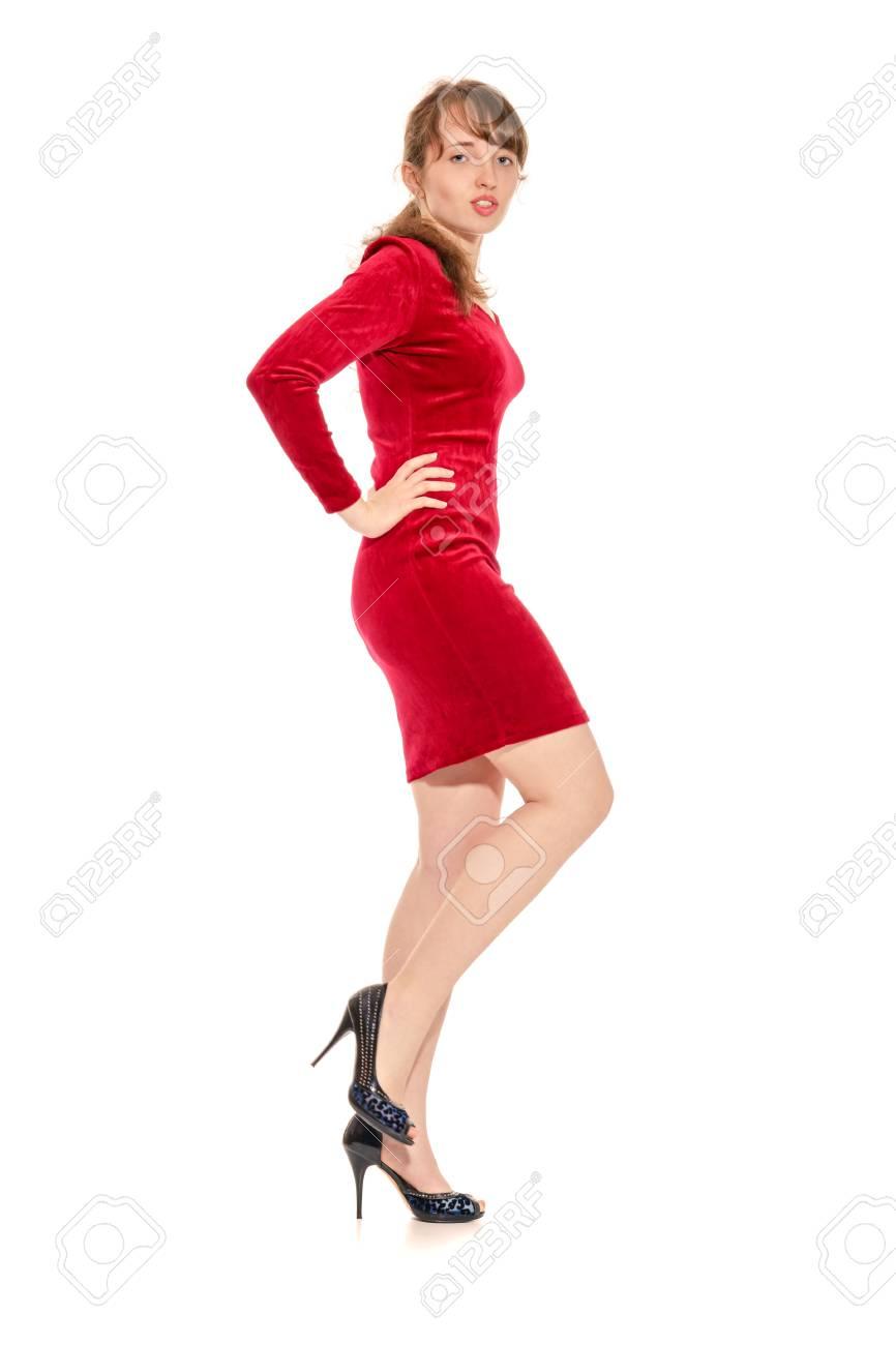 4159ac40d0cb75 Het verleidelijke meisje in de rode stiekeme jurk en in schoenen op een hoge  hak.