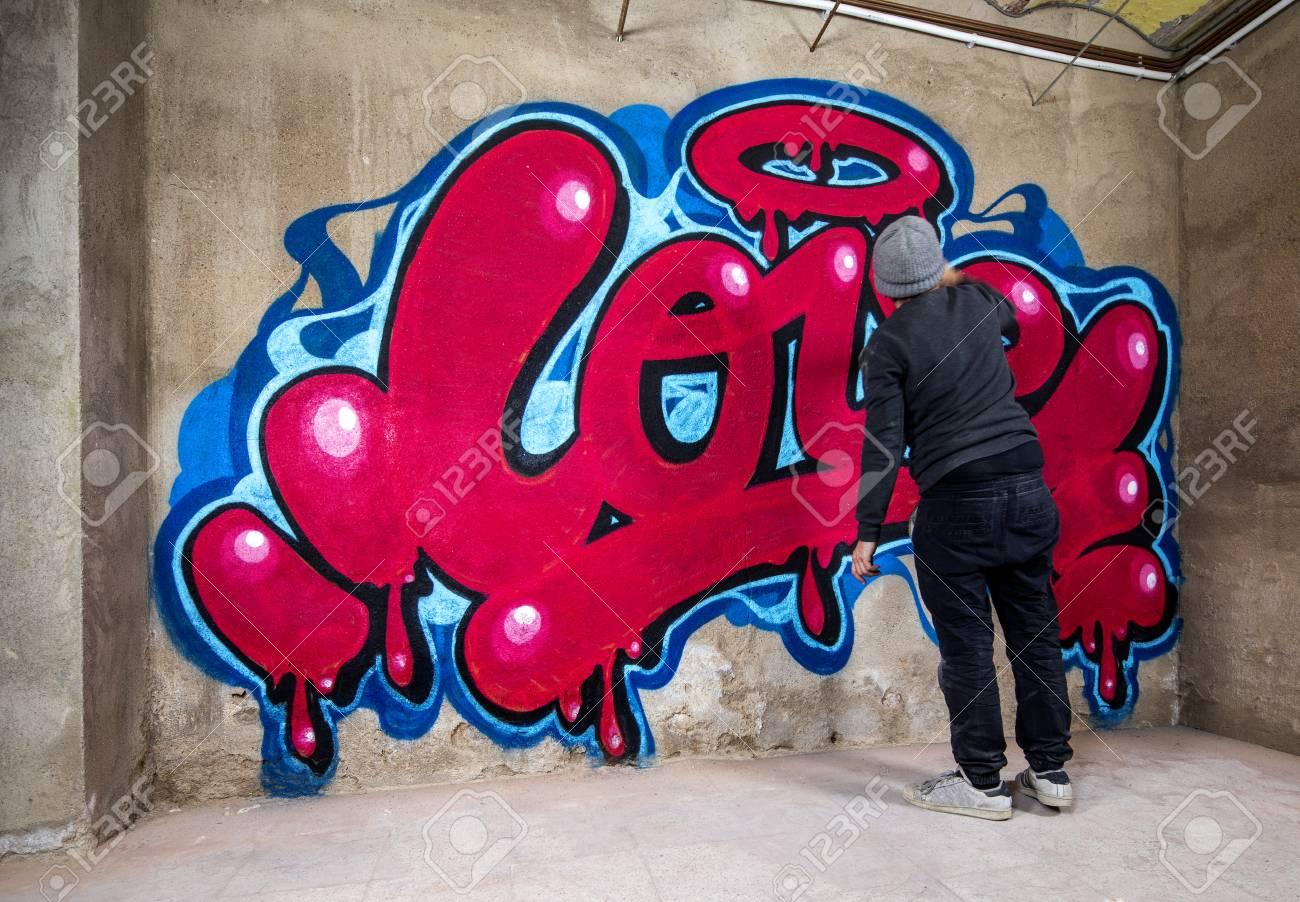 graffiti artist spraying the word love on a wall