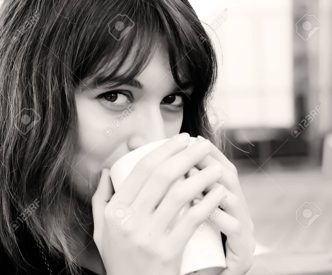 young girl with a cup of coffee. Focus on the eyes. Stock Photo - 12441348
