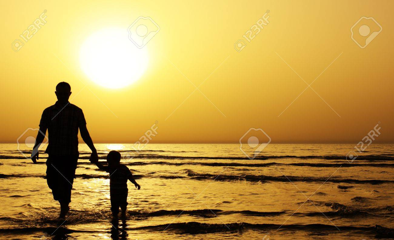 child with his father at sea. Sunset Stock Photo - 12441484