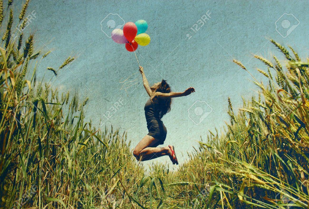 Young woman holding colorful balloons and flying over a meadow   Photo in old color image style Stock Photo - 13562884