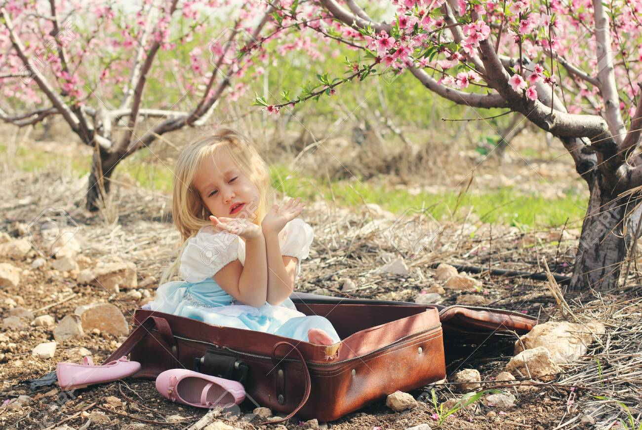 5c2841d316aa Cute girl wearing a blue dress sitting in vintage bag and dancing Stock  Photo - 38260649