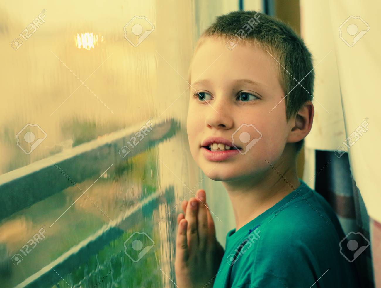 Cute 10 Year Old Autistic Boy Looking At The Rain Stock Photo