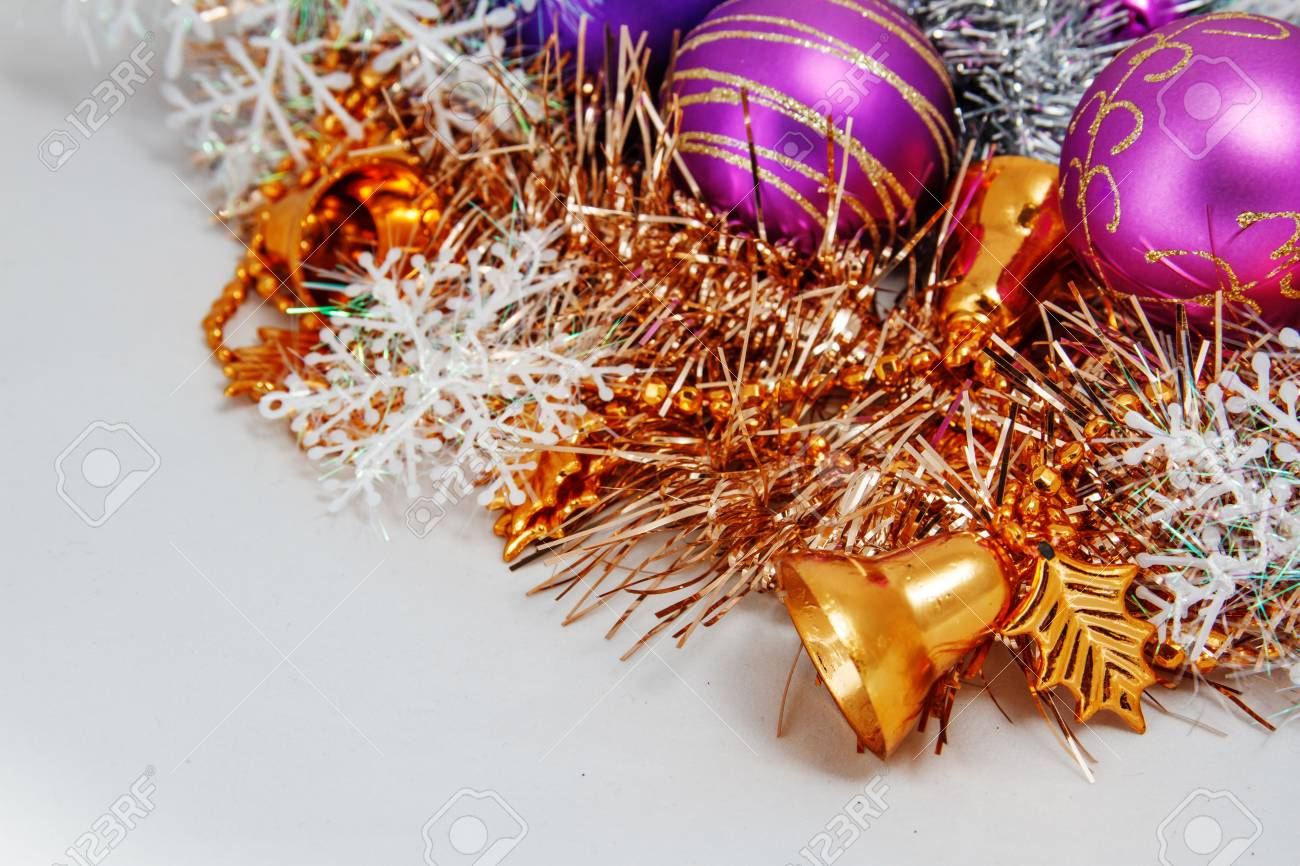 christmas decoration of tinsel christmas balls snowflakes beads and bells and a wooden