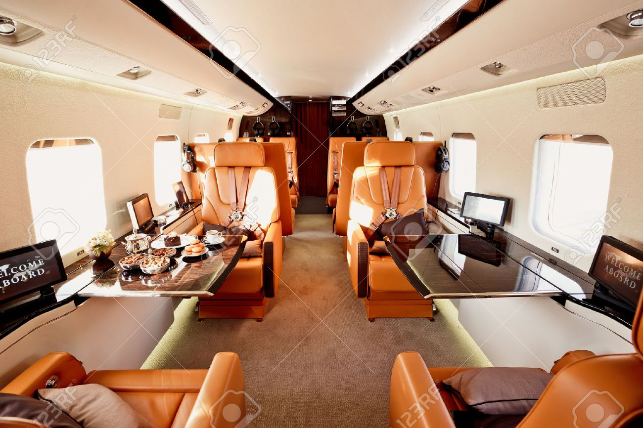 private plane interior with wooden tables and leather seats stock