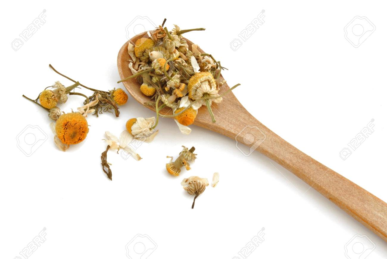Chamomile leaves on a wooden spoon isolated on white background Stock Photo - 9770440
