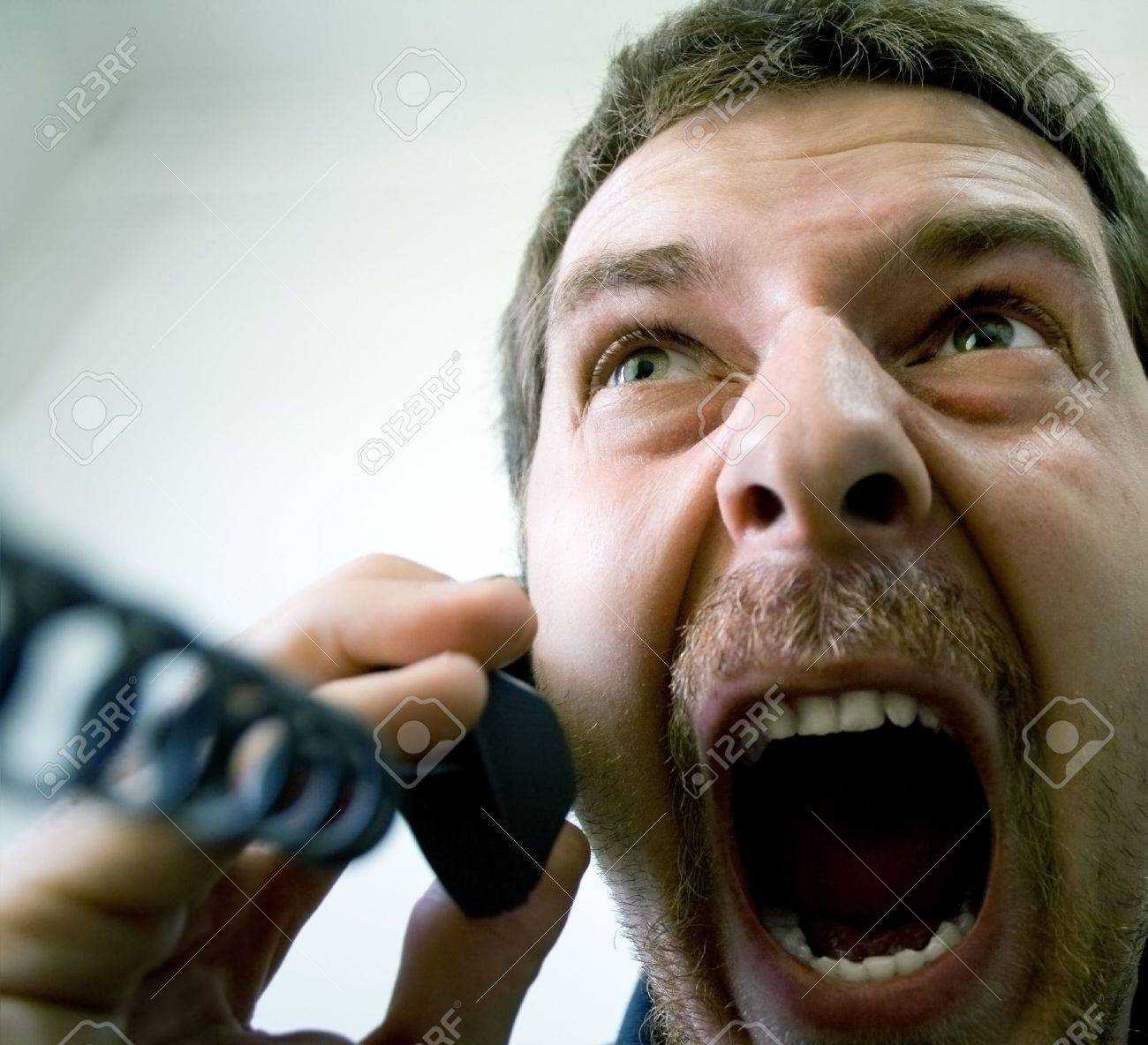 Portrait of angry stressed businessman screaming at the phone Stock Photo - 3836608