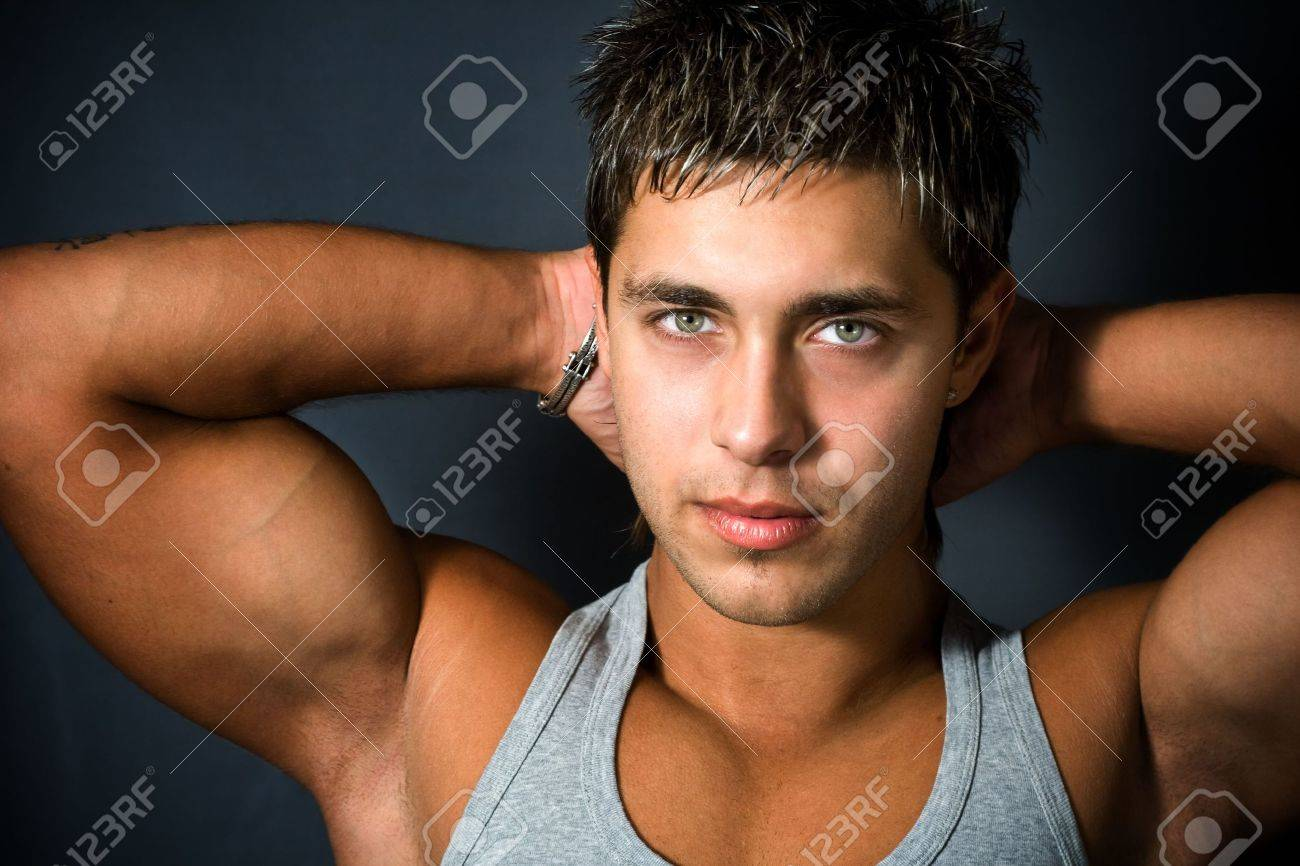 Portrait Of Sexy Young Man Showing His Muscular Arms Stock Photo