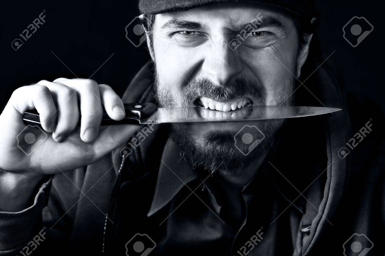 Tough angry guy biting from sharp knife Stock Photo - 4204993