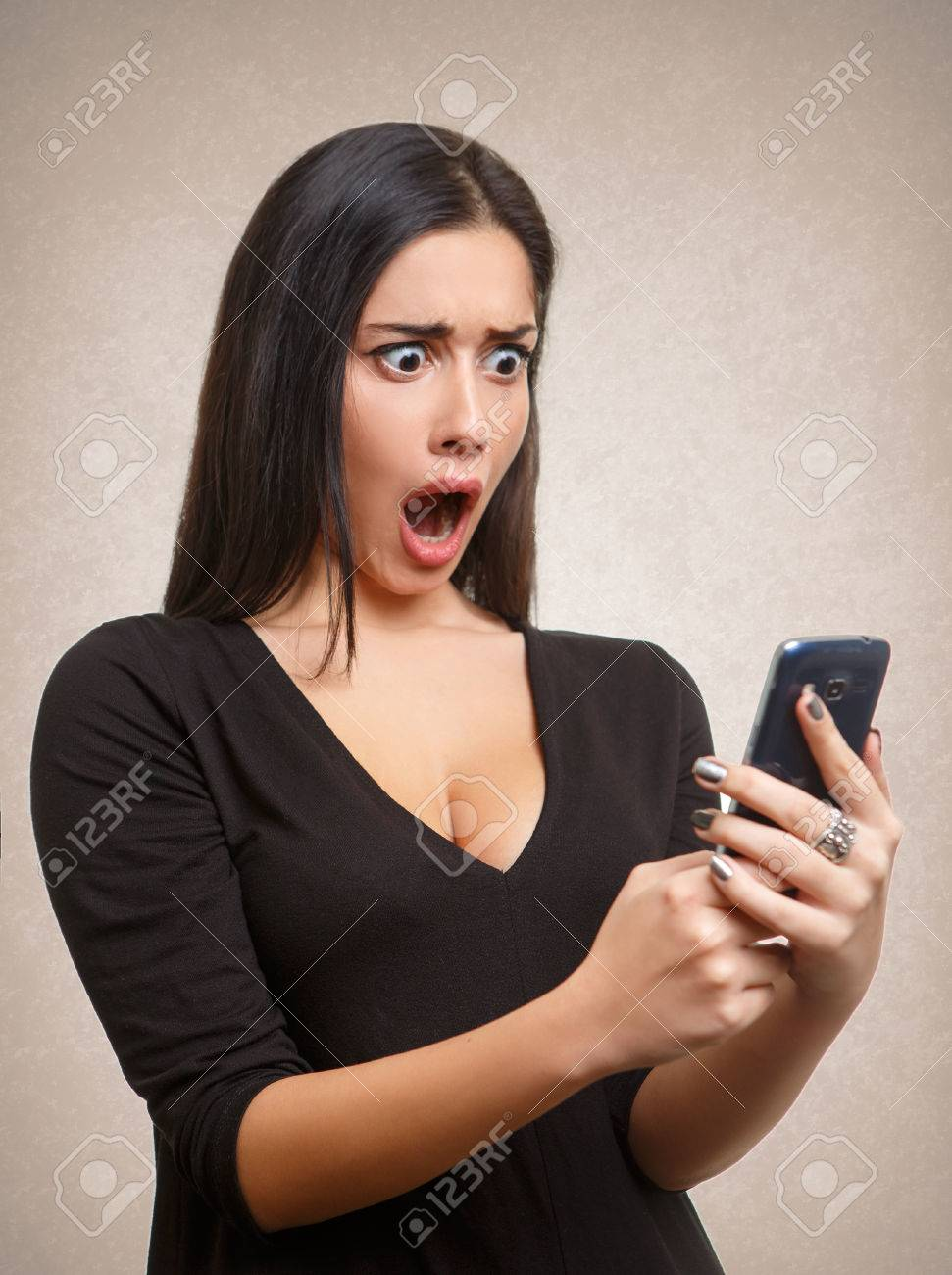 Young woman shocked by mobile phone news or message Stock Photo - 55148569