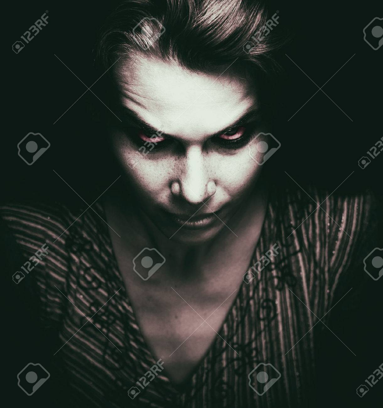 Face of scary woman with evil eyes in the dark Stock Photo - 55776128