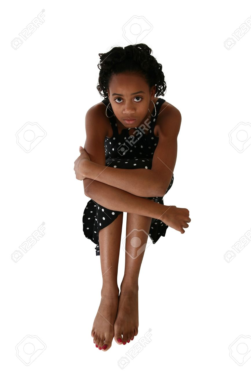 Beautiful African Amercian 15 year old Teen Girl sitting barefoot in dress over white. Stock Photo - 2272957