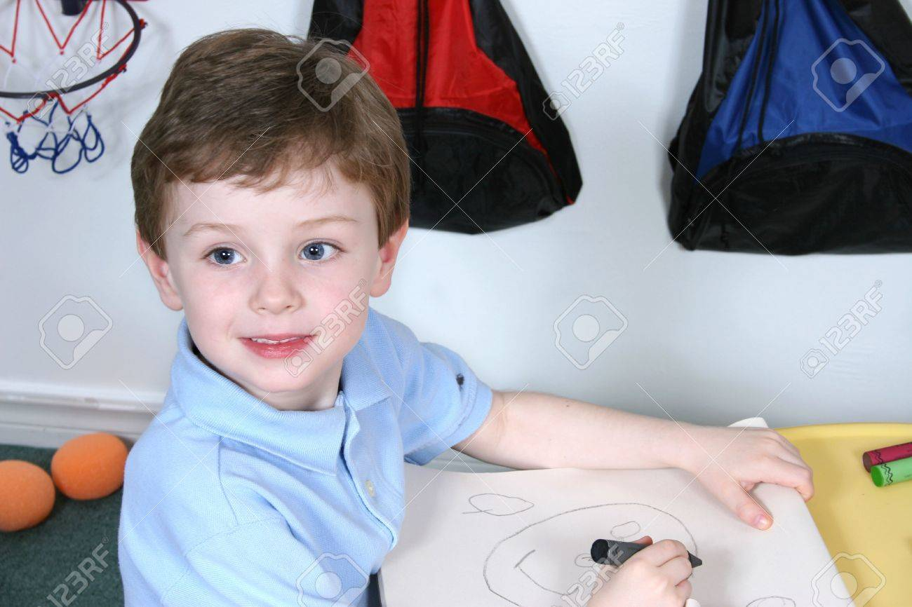 Handsome And Happy Little Boy Sitting At A Pre School Table Coloring With Jumbo Crayons