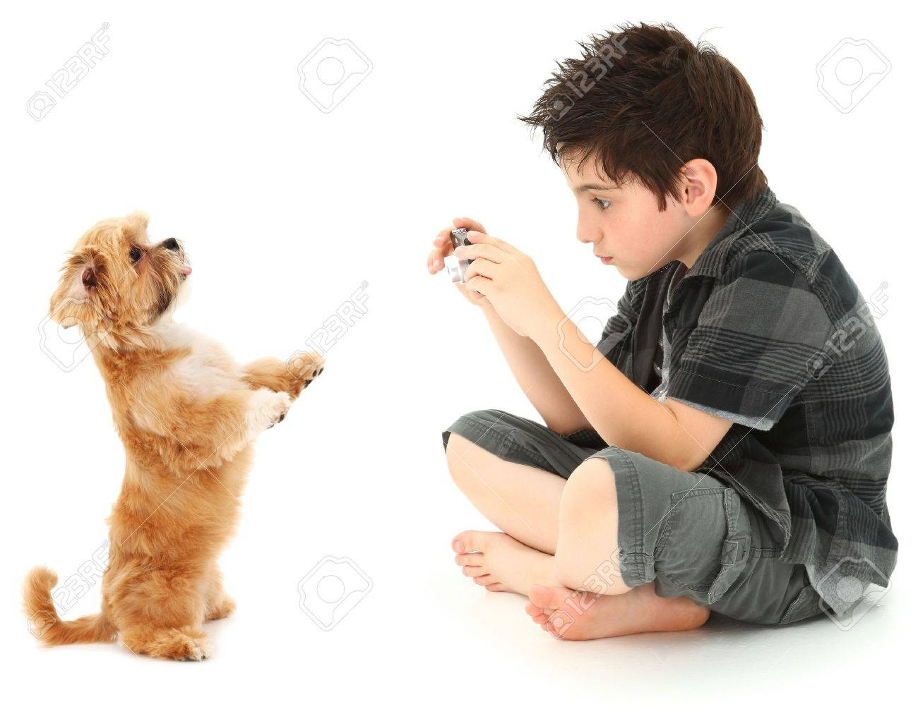 Adorable 8 year old boy shooting photos of his dog with digital camera over white background. Stock Photo - 9739090