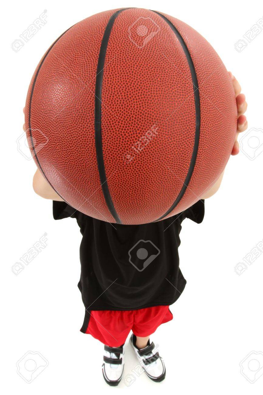 Top view of basket ball playing boy child ready to throw ball.  Close up view ball covering child's face. Stock Photo - 9885272