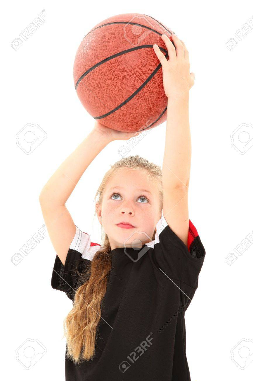 adorable female child making free throw with basketball in uniform