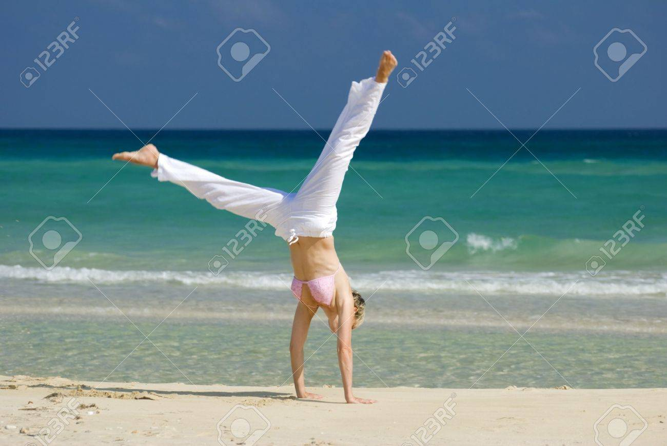 young blond woman making cartwheel on the beach Stock Photo - 2880388