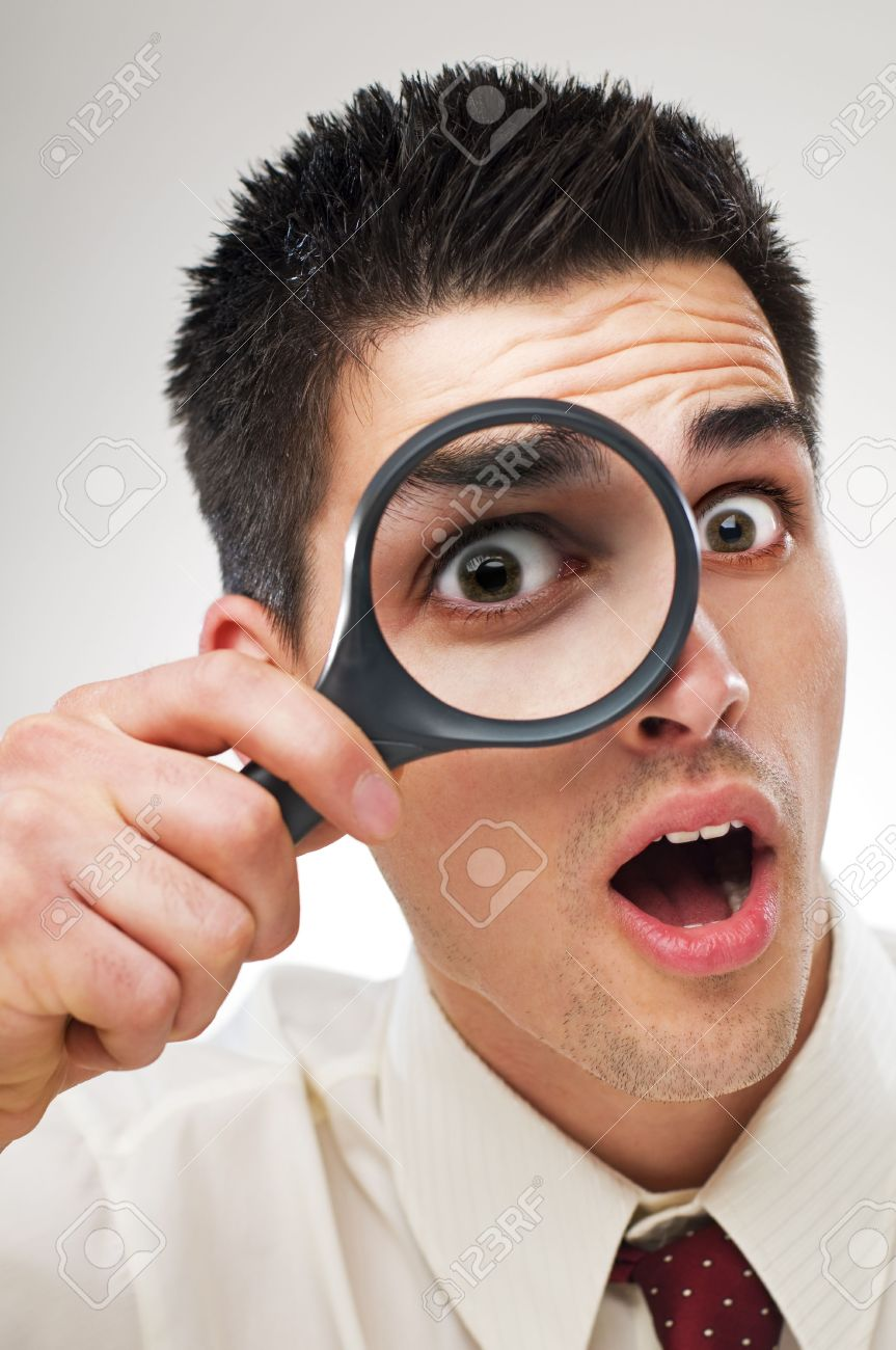 surprised young business man looking through loupe close up Stock Photo - 4634826