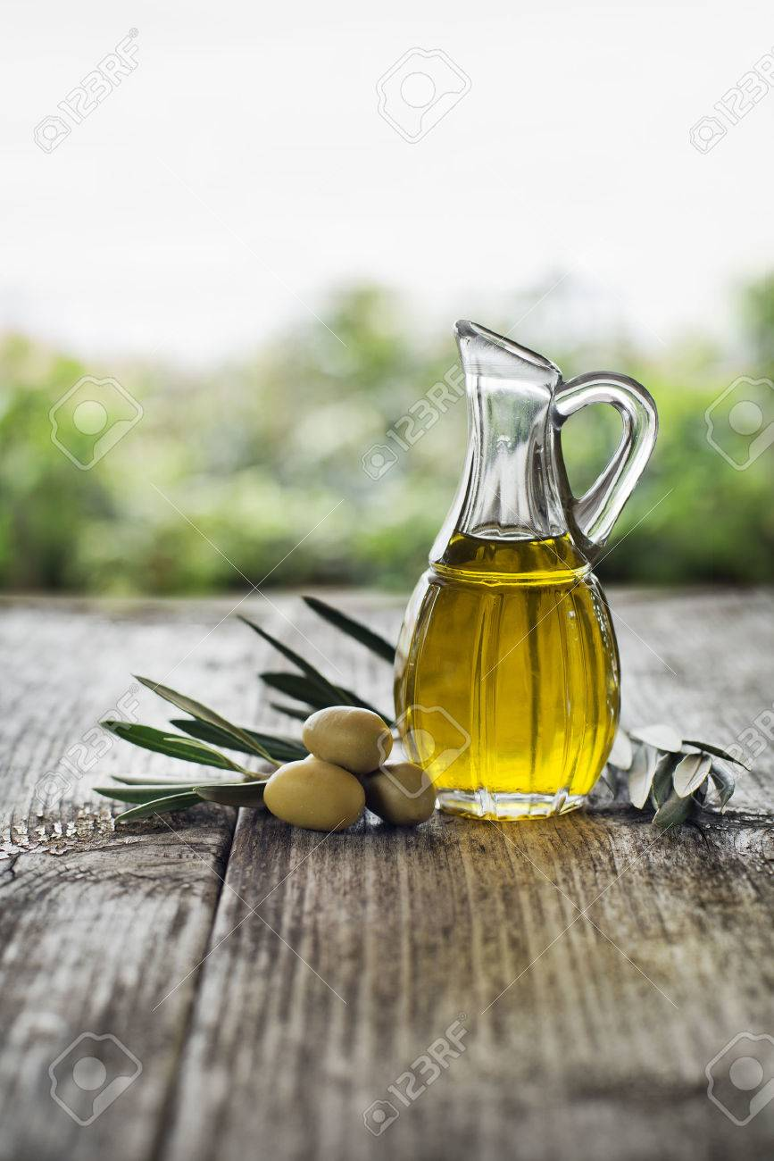 Olive oil and olive branch on the wooden table - 34200735